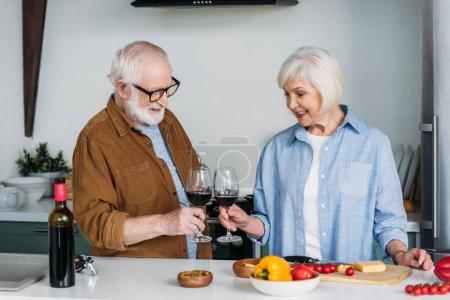 Photo pour Heureux couple aîné avec des verres à vin griller près de la table avec de la nourriture dans la cuisine - image libre de droit
