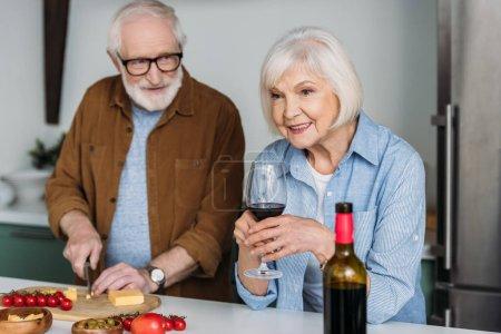 Photo pour Mari aîné souriant regardant femme avec verre à vin tout en coupant le fromage sur planche à découper dans la cuisine sur fond flou - image libre de droit
