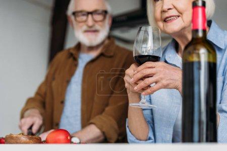 Photo pour Senior femme tenant verre de vin près de la bouteille avec l'homme flou sur fond intérieur - image libre de droit