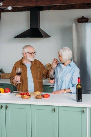 Photo pour Mari âgé souriant avec verre à vin alimentation femme avec morceau de fromage dans la cuisine - image libre de droit