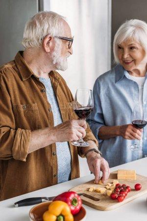 Photo pour Couple âgé souriant avec verres à vin se regardant près de la table avec du fromage et des légumes dans la cuisine - image libre de droit