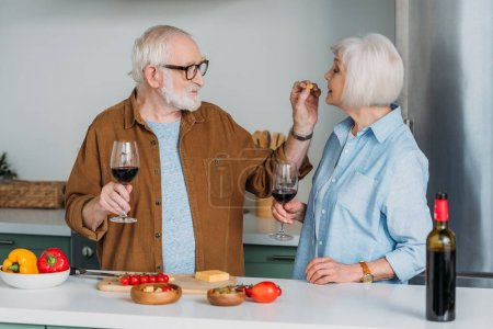 Photo for Smiling senior man with wine glass feeding wife with piece of cheese in kitchen on blurred background - Royalty Free Image