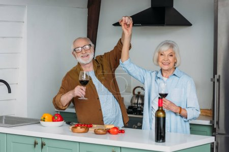 happy senior couple with wine glasses looking at camera while having fun near table with food in kitchen