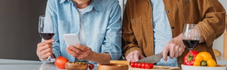 cropped view of elderly husband cooking dinner near wife with wine glass and smartphone in kitchen, banner