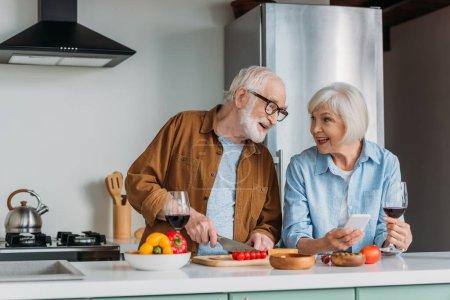 Photo pour Heureux couple âgé regardant l'autre près de la table avec de la nourriture et des verres à vin dans la cuisine - image libre de droit