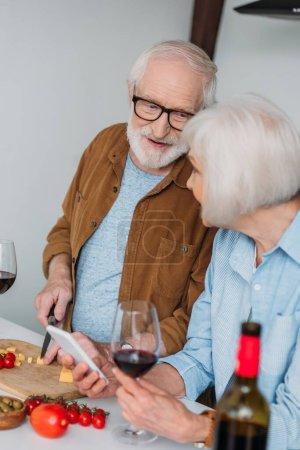 mari aîné souriant regardant sa femme tout en coupant du fromage sur une planche à découper près des légumes au premier plan flou