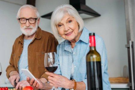 Photo pour Femme âgée souriante avec smartphone et verre à vin regardant la caméra près du mari avec bouteille floue au premier plan à l'intérieur - image libre de droit
