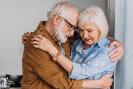 Photo pour Heureux couple aîné avec les yeux fermés étreignant à l'intérieur - image libre de droit