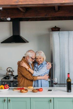 Photo pour Heureux couple âgé étreignant près de la table avec de la nourriture et des verres à vin dans la cuisine - image libre de droit