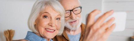 Photo pour Joyeuse femme âgée regardant la caméra tout en prenant selfie avec l'homme sur le premier plan flou à l'intérieur, bannière - image libre de droit