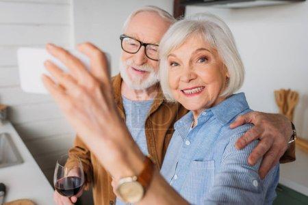 Photo pour Heureuse femme âgée regardant la caméra tout en prenant selfie avec mari tenant verre de vin à l'intérieur sur le premier plan flou - image libre de droit