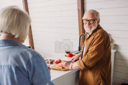 Photo pour Heureux homme âgé regardant caméra tout en coupant du fromage avec femme floue au premier plan dans la cuisine - image libre de droit