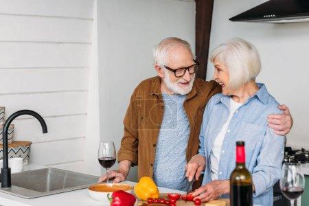 Foto de Feliz marido mayor abrazo y mirando esposa cocina cena en cocina borrosa en primer plano - Imagen libre de derechos