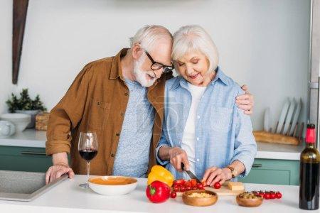 Photo pour Mari aîné souriant étreignant femme cuisine le dîner sur la table avec du vin, du fromage et des légumes sur fond flou - image libre de droit