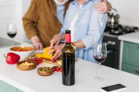 cropped view of elderly couple near table with bottle of wine and vegetarian food on blurred background