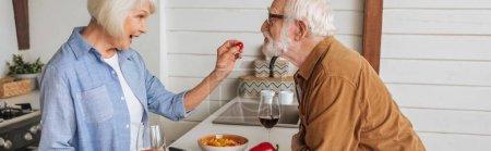 Photo pour Vue latérale de heureuse femme âgée nourrissant mari avec tomate cerise dans la cuisine, bannière - image libre de droit