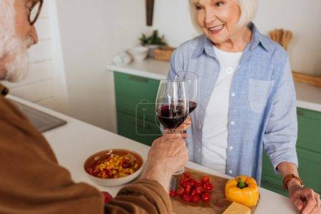 Photo pour Heureux couple âgé griller avec des verres à vin près de la table avec de la nourriture au premier plan flou - image libre de droit