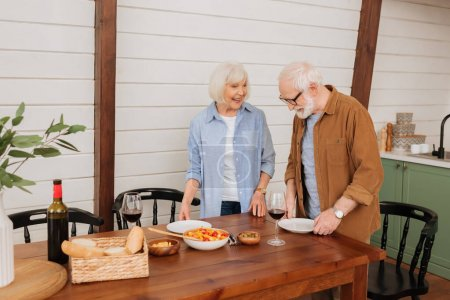 Photo for Happy senior couple serving table with plates in kitchen - Royalty Free Image