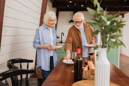 Photo for Smiling senior couple serving table with plates and salad in kitchen with blurred decorative plant on foreground - Royalty Free Image