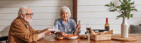 Lächelnde Seniorin mit Spachtel serviert Salat für Ehemann am Tisch mit vegetarischem Abendessen in der Küche, Banner