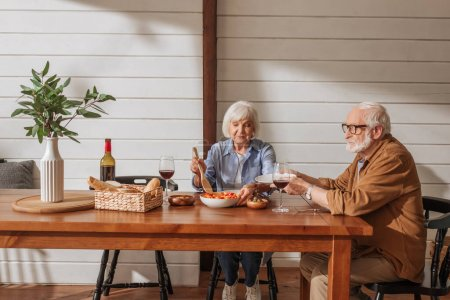 Photo for Happy senior wife with spatula serving salad for husband at table with vegetarian dinner in kitchen - Royalty Free Image