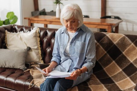 senior woman looking at bills while sitting on couch on blurred background in living room