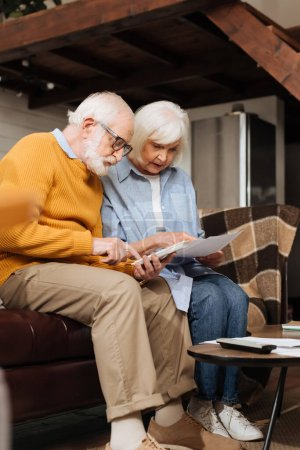 senior husband counting on calculator near wife looking at bills on couch on blurred background in living room
