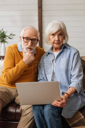 thoughtful senior couple with laptop looking at camera while sitting on couch on blurred background at home