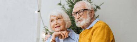 älterer Mann schaut weg, während er lächelnde Frau auf der Terrasse auf verschwommenem Hintergrund umarmt, Banner