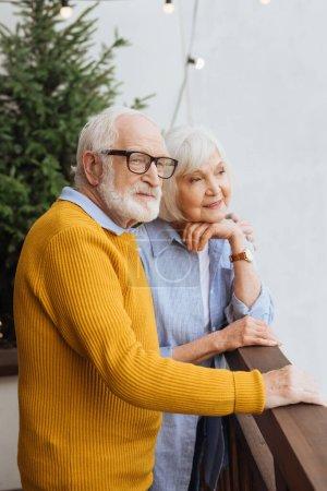 Senior Ehemann umarmt lächelnde Frau, während er auf der Terrasse vor verschwommenem Hintergrund wegschaut