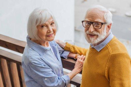 Hochwinkelaufnahme eines lächelnden Seniorehepaares, das auf der Terrasse auf verschwommenem Hintergrund in die Kamera blickt