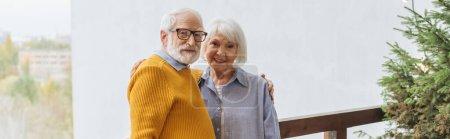 Lächelndes älteres Paar blickt in die Kamera, während es sich auf der Terrasse vor verschwommenem Hintergrund umarmt, Banner