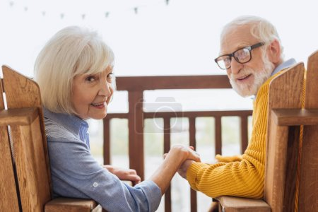 smiling elderly couple looking at camera and holding hands while sitting in armchairs on terrace on blurred background