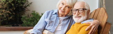 lächelnde Seniorin umarmt Ehemann und blickt auf der Terrasse auf verschwommenem Hintergrund in die Kamera, Banner