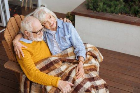 Lächelndes älteres Paar mit karierter Decke, das sich umarmt und wegschaut, während es im Sessel auf der Terrasse vor verschwommenem Hintergrund sitzt
