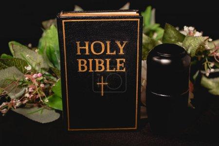 Photo pour Sainte Bible et urne avec cendres sur fond noir, concept funéraire - image libre de droit