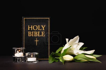 Foto de Lirio, velas y la Biblia santa sobre fondo negro, concepto de funeral - Imagen libre de derechos