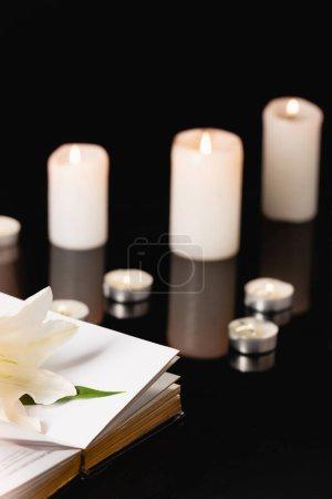 Photo pour Lys, bougies et bible sainte sur fond noir, concept funéraire - image libre de droit