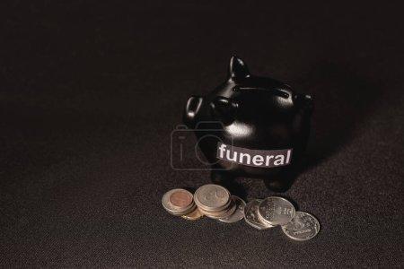 Foto de Alcancía con monedas sobre fondo negro, concepto de funeral - Imagen libre de derechos