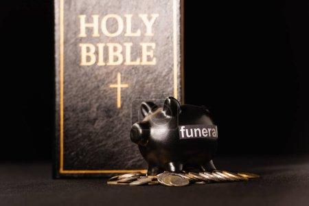 Photo pour Tirelire avec pièces de monnaie et bible sainte sur fond noir, concept funéraire - image libre de droit