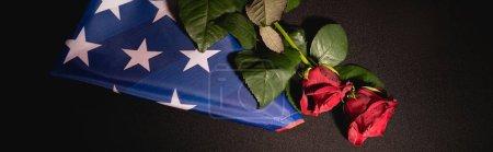 Draufsicht auf rote Rosen und amerikanische Flagge auf schwarzem Hintergrund, Bestattungskonzept, Banner