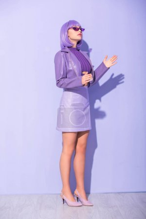 Photo pour Jeune femme habillée dans le style poupée sur fond violet coloré - image libre de droit