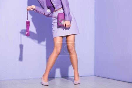 vue partielle de la jeune femme vêtue de style poupée avec téléphone rétro sur fond violet coloré