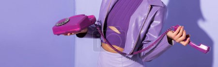 vue recadrée de jeune femme vêtue de style poupée avec téléphone rétro sur fond violet coloré, bannière
