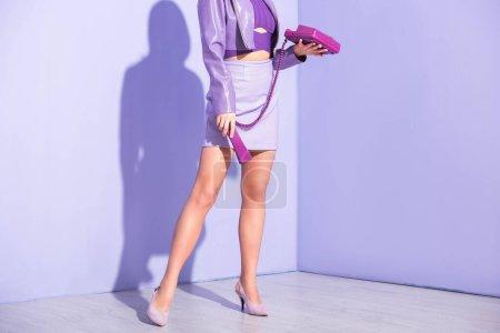 vue recadrée de jeune femme vêtue de style poupée avec téléphone rétro sur fond violet coloré