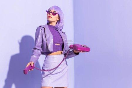 jeune femme habillée dans le style poupée avec téléphone rétro sur fond violet coloré