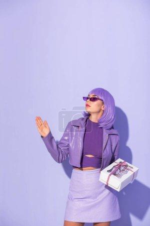 junge Frau im Puppenstil mit Cupcake-Box auf violettem Hintergrund gekleidet