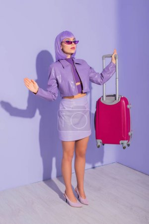 young woman dressed in doll style with luggage on violet colorful background