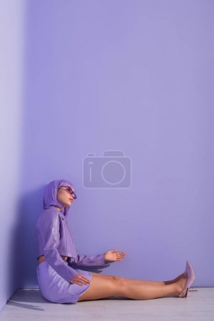Photo for Young woman dressed in doll style sitting on floor on violet colorful background - Royalty Free Image
