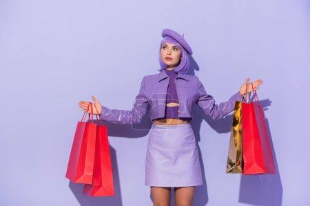 Photo pour Jeune femme habillée dans le style poupée avec des sacs à provisions rouges sur fond violet coloré - image libre de droit